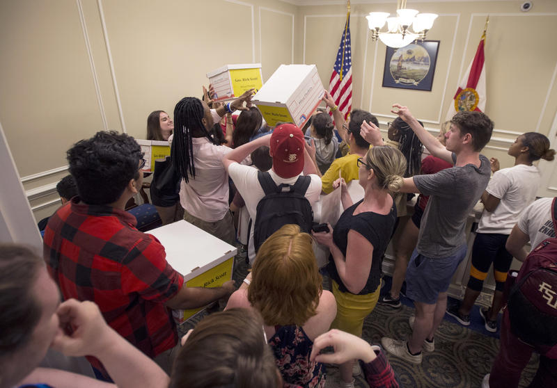 University students pass around boxes of petitions for Florida Governor Rick Scott in the governor's office inside the Florida Capitol in Tallahassee, Fla., Feb 21, 2018.