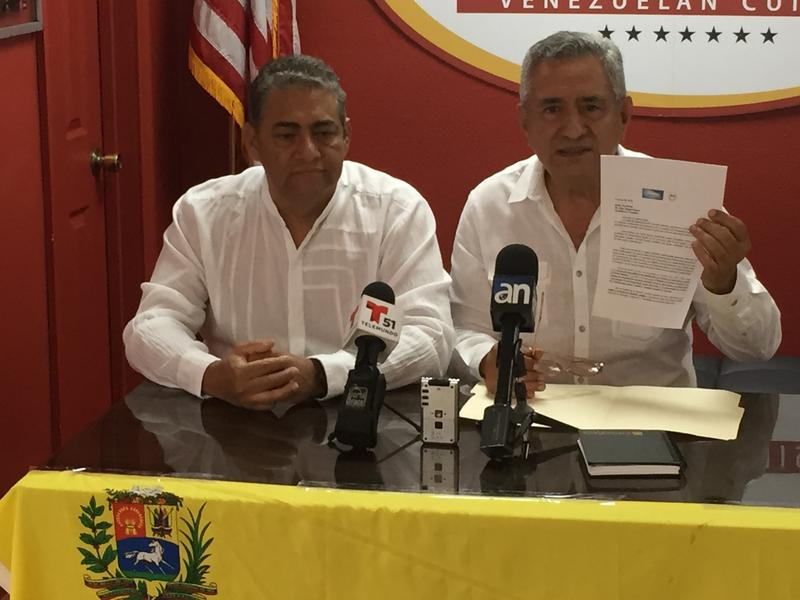 Pablo Medina (right) and Rafael Moros of the International Coalition for Venezuela at the Arepazo Dos in Doral on Wednesday, with their letter calling for recognition of the refugee crisis on Colombia's border.