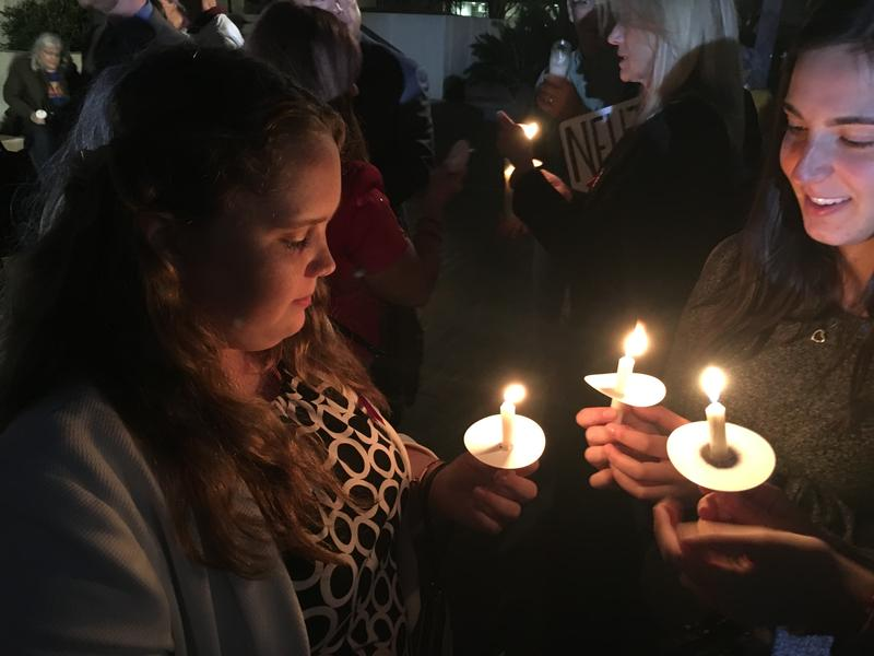 Marjory Stoneman Douglas High School sophomore Annabel Claprood and her friends hold a candle before a vigil for the victims at the Feb. 14 shooting held at the Capitol on Tuesday.