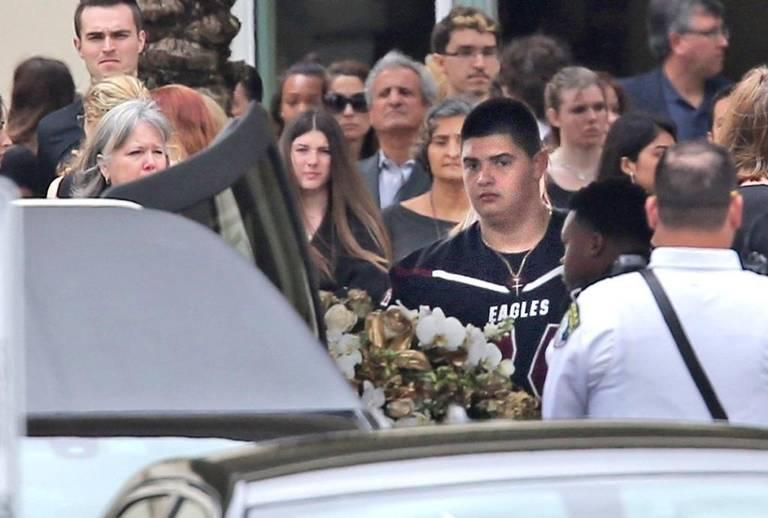 Football players put the casket in the hearse at the funeral for Aaron Feis, the Marjory Stoneman Douglas High School security guard and assistant football coach who died while shielding students from the shooter on Feb. 14, 2018.