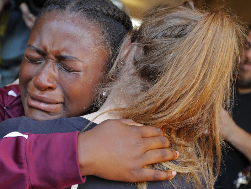 Marla Eveillard, 14, cries as she hugs friends before the start of a vigil at the Parkland Baptist Church, for the victims of Wednesday's shooting at the Marjory Stoneman Douglas High School in Parkland, Fla., Thursday, Feb. 15, 2018.
