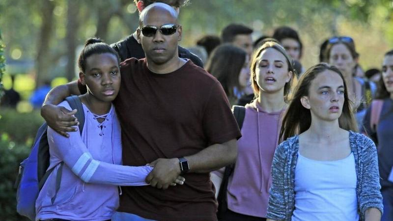Students and parents leave campus after a gunman opened fire at Marjory Stoneman Douglas High School on Wednesday.