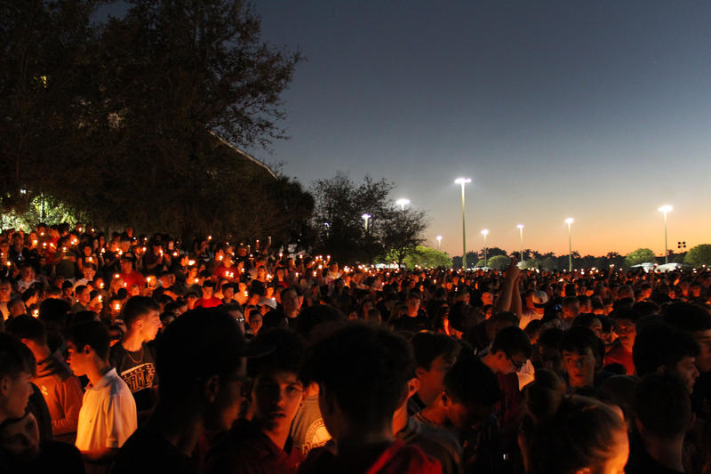 Students and others associated with Marjory Stoneman Douglas High School in Parkland gather for a vigil on Thursday, honoring the 17 people killed there on Wednesday when a gunman opened fire.