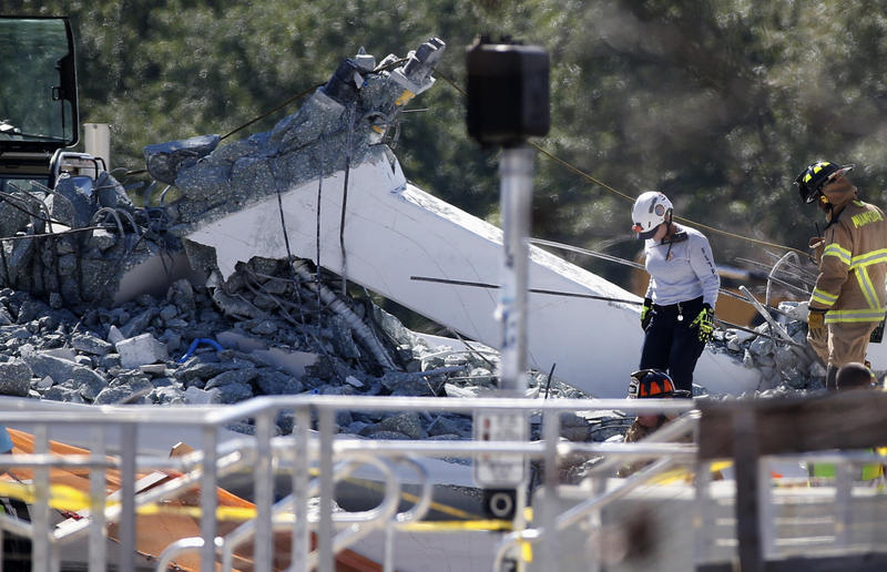 Rescue workers walk on the rubble after a brand-new pedestrian bridge collapsed at Florida International University in Miami on Thursday, March 15, 2018.