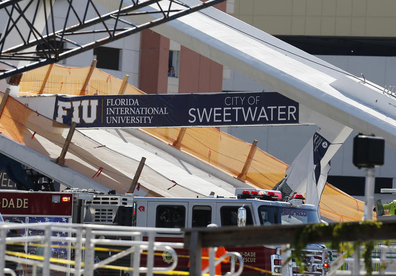A sign above the rubble of a new pedestrian bridge is shown after the bridge collapsed onto a highway at Florida International University in Miami on Thursday, March 15, 2018.