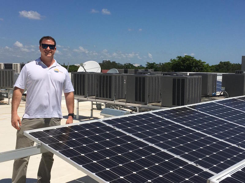 Daren Goldin stands with one of his company's solar installations on a Coconut Grove hotel roof.