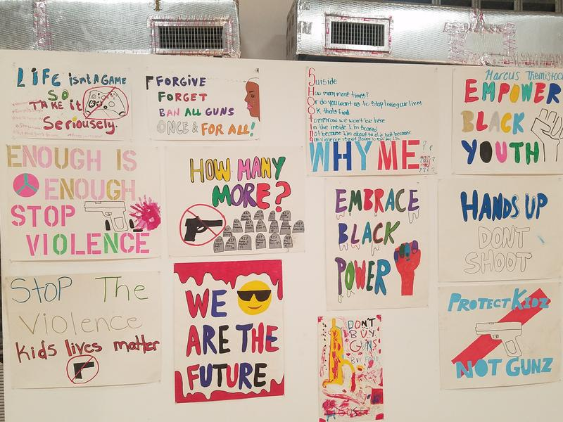 Signs created by students who participated in the walkout for the 19th anniversary of the Columbine High School shooting on display during the Hip Hoppa Locka Block party.