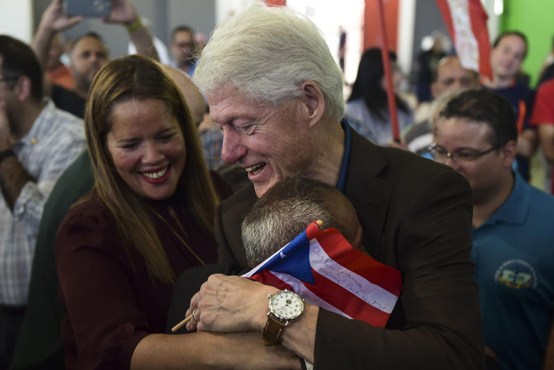 Former President Bill Clinton hugs a resident living at the William Rivera Betancourt Vocational School which was turned into an emergency shelter for families affected by the impact of Hurricane Maria, in Canovanas, Puerto Rico, Monday, Nov. 20, 2017.