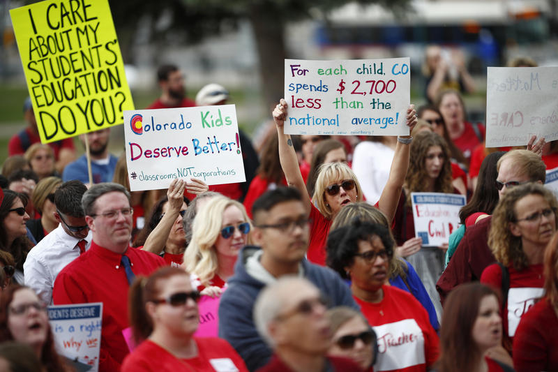 Teachers hold placards during a rally outside the state Capitol, Monday, April 16, 2018, in Denver, Colorado.