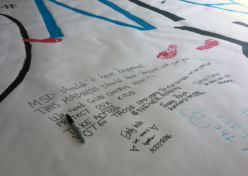 "MSD students made a ""Never Again"" poster with personal messages to send to Columbine High."