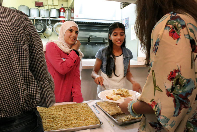 Ghuzlan Fayyad (left) and Sedra Haboub serve desserts like baklava to their guests at the Coral Gables Congregational Church during A Taste of Sryria, an event hosted by O, Miami for poetry month that aims to help Syrian refugees build community.