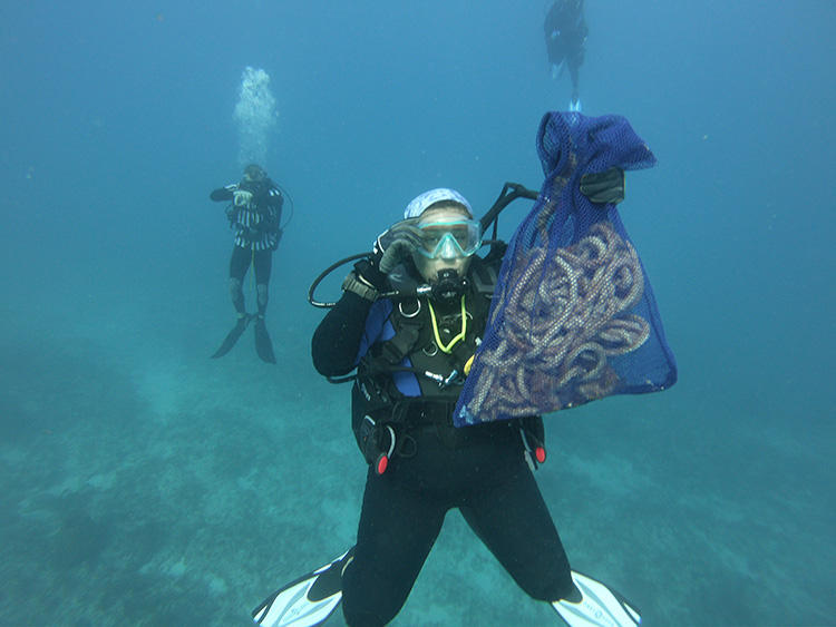 A diver brings up a trapline collected during a marine debris cleanup in the Keys.