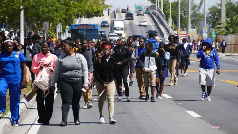 Students from Northwestern High march into the Liberty Square neighborhood where four young men were shot Sunday afternoon.