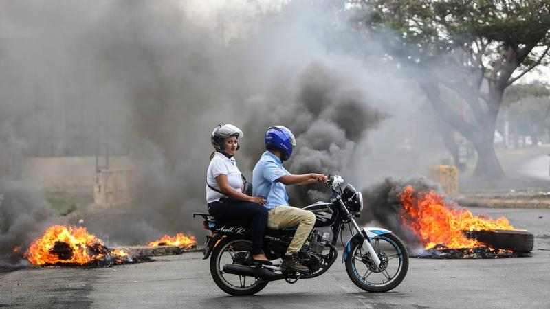 People on a motorcycle pass a burning barricade during clashes near the University Politecnica de Nicaragua (UPOLI) in Managua, Nicaragua, Saturday, April 21, 2018.
