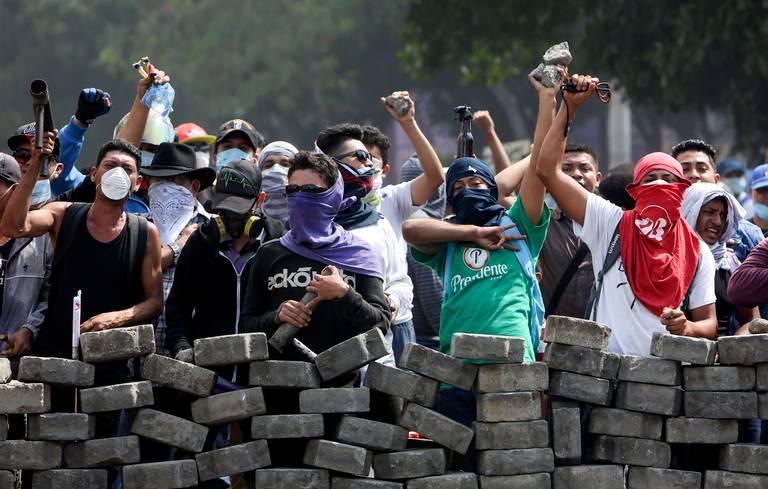 SOMOZA TO SANDINISTAS: Protesters behind barricades demonstrate against Nicaraguan President Daniel Ortega in Managua this week.
