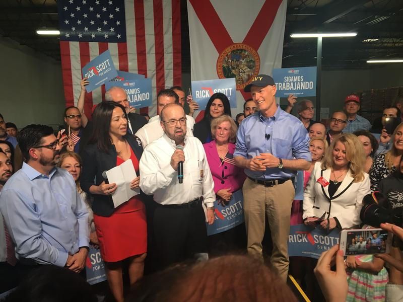 Alvaro Lozano, president of Interstate Beverage Corporation, at the warehouse of which the rally was held, introduces Governor Rick Scott.