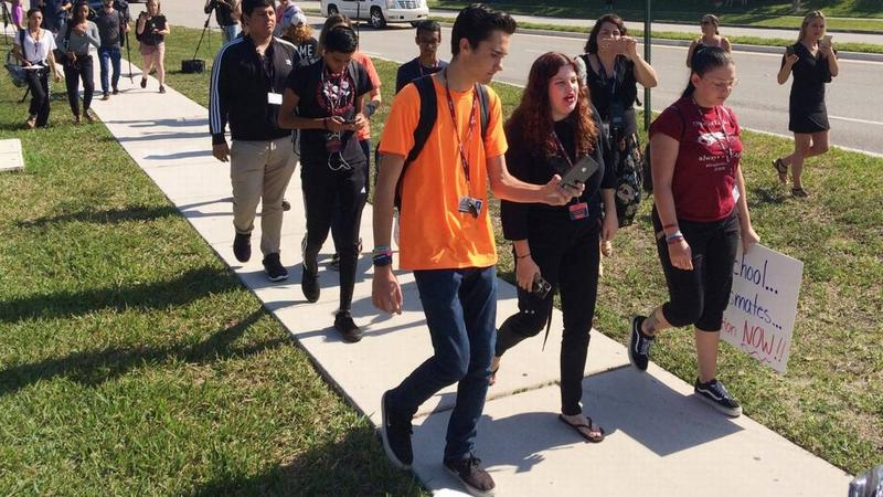 David Hogg, left, a student activist at  Marjory Stoneman Douglas High School, speaks to a student as they walk out of their school, Friday, April 20, 2018 in Parkland, Fla.