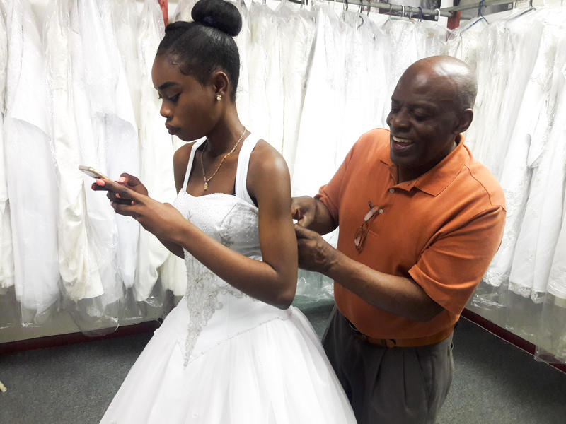 Rollin Virgile adjusts a dress for a young woman who drove from Key West to visit his store.