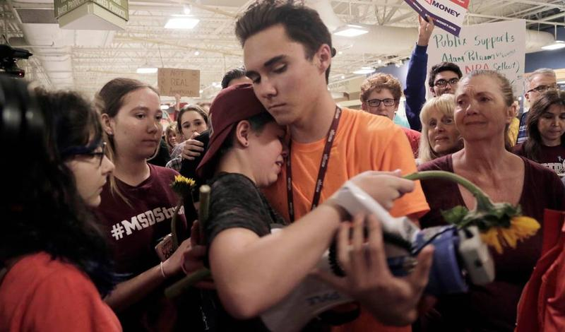 """David Hogg hugs a fellow protester after the demonstration ended inside the store. Protesters spread out on the floor of the Publix store in Coral Springs Friday, May 25, 2018, for a 12 minute """"die-in"""" to protest Publix's support for Adam Putnam"""