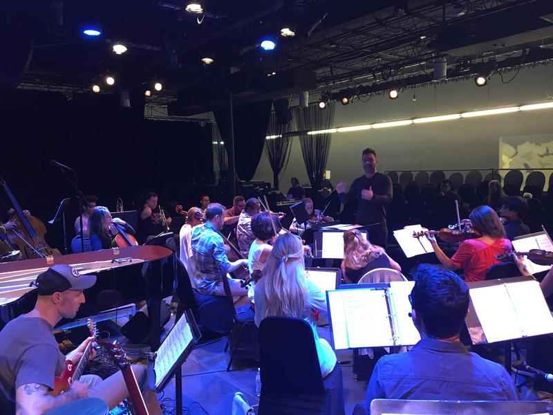 Conductor Jacomo Bairos leads the rehearsal.