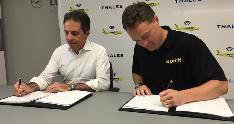 CEO of Thales InFlyt Experience Dominique Giannoni, left, and Spirit Airlines President and Chief Financial Officer Ted Christi, right, sign the partnership contract to install Wi-Fi on all Spirit planes.