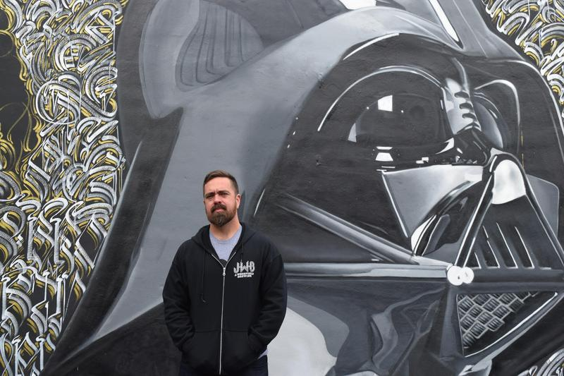Jonathan Wakefield poses in front of a mural on one of the exterior walls of his brewery, J. Wakefield Brewing in Wynwood.