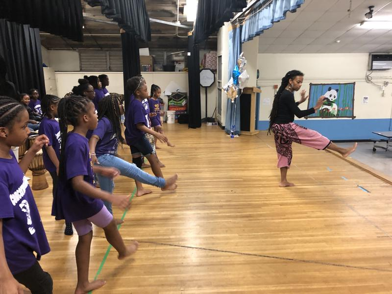 Teacher Asha Darbeau, right, directs her dance class in a warmup.