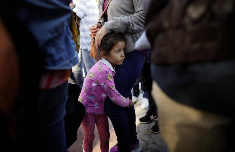 A Central American girl waits with her family at the U.S. border at Tijuana, Mexico, to request asylum.