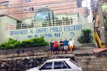 """Tourists pose for a photo at one of the stops on a Medellin narco tour, in front of a sign that says """"Welcome to Pablo Escobar's Neighborhood"""""""