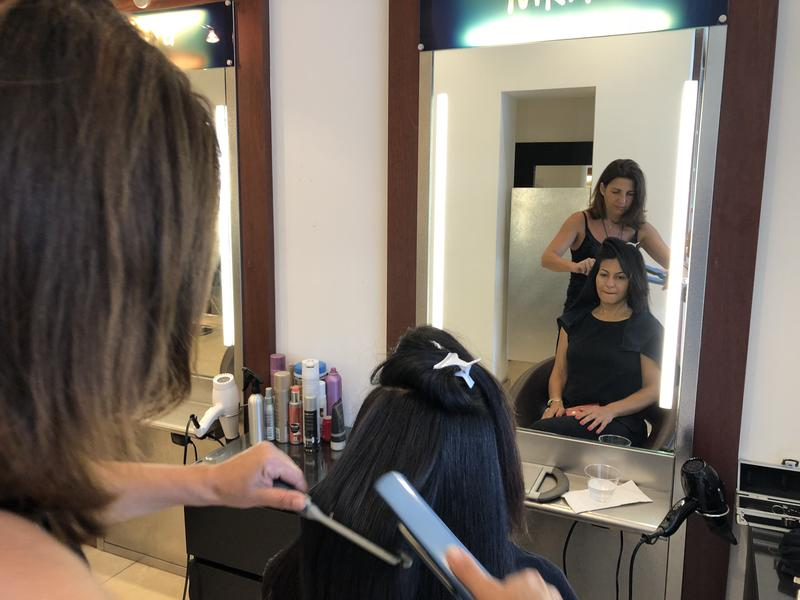 Valérie Nedjar, a French stylist, straightens a client's hair at Nikita Salon, in South Miami, Fl.