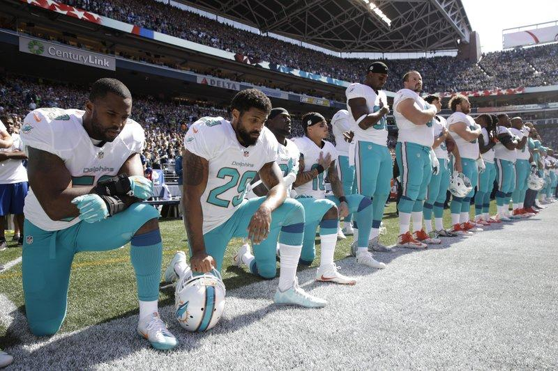 From left, Miami Dolphins' Jelani Jenkins, Arian Foster, Michael Thomas, and Kenny Stills, kneel during the singing of the national anthem before an NFL football game against the Seattle Seahawks in Seattle, on Sept. 11, 2017.