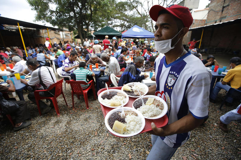 "In this Feb. 23, 2018 photo, a volunteer at the ""Divina Providencia"" migrant shelter distributes lunch to Venezuelan migrants, in Cucuta, Colombia. The food is cooked in several large vats and the diocese says it offers an average of 1000 meals a day."
