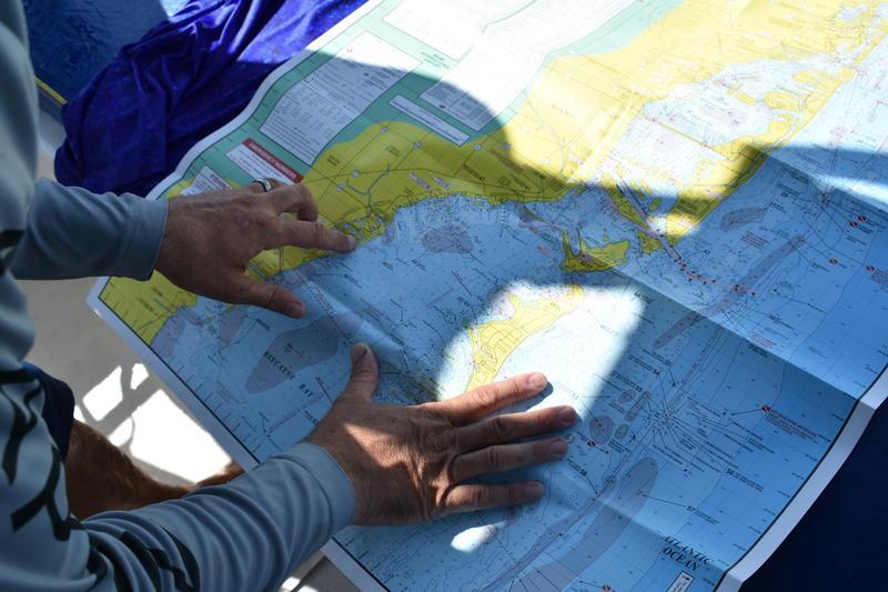 Captain Hans Bockelman studies a map of Biscayne Bay.