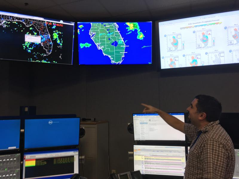 SFWMD operations control specialist Ariosto Munoz alters the flow of water from a control room in the West Palm Beach headquarters.