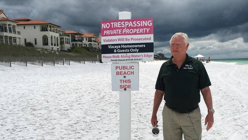 In this May 15, 2018, photo Bill Hackmeyer walks on the beach near his condo, in Santa Rosa Beach, Fla. He  defends his fight to keep the public off of the private beach in front of his gated community.