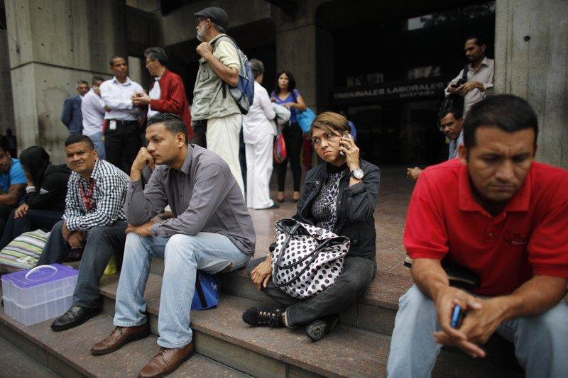 Office workers in Caracas leave their building during massive blackouts on Tuesday that left some 80 percent of the metropolis without power.