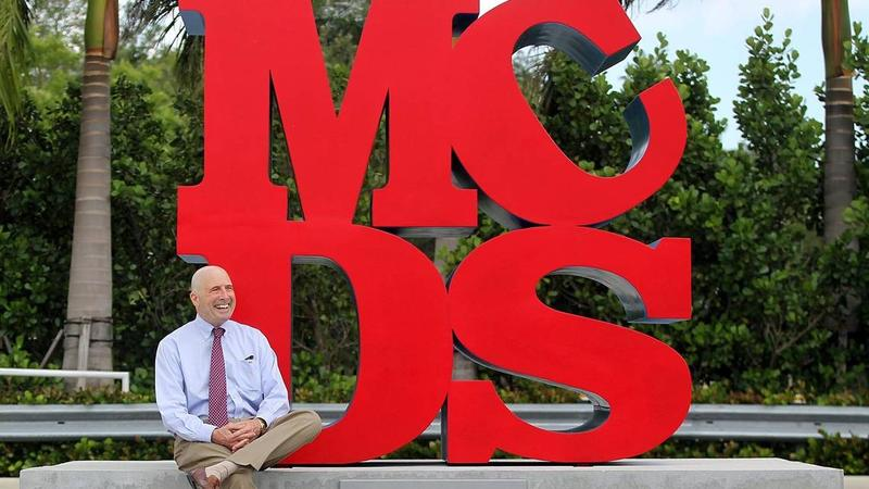 Outgoing principal John Davies sits next to an on-campus sculpture he designed after being inspired by artist Robert Indiana. He argued he has taken students' concerns about a culture of racism at the school seriously.