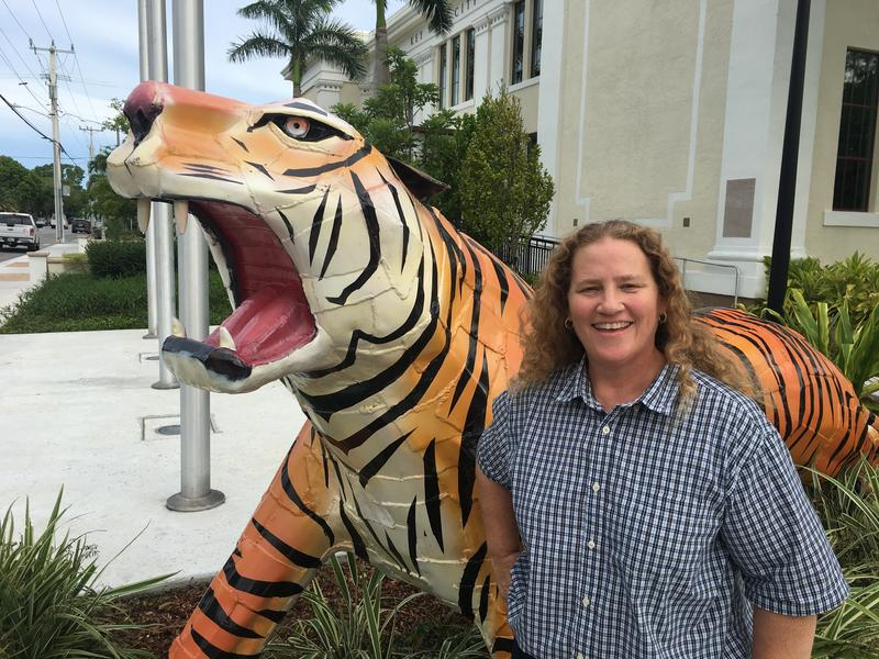 Joy Nulisch with the tiger statue designed by her late stepfather, George Carey. Originally the mascot for Frederick Douglass High School, the tiger stands in front of what is now Key West City Hall.