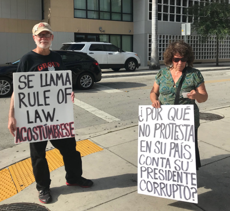 """Josefina Rosenthal says she came from Cuba and thinks immigrants shouldn't protest any U.S. president. Her sign says: """"Why not protest in your country against [conta - sic] your corrupt president?"""""""