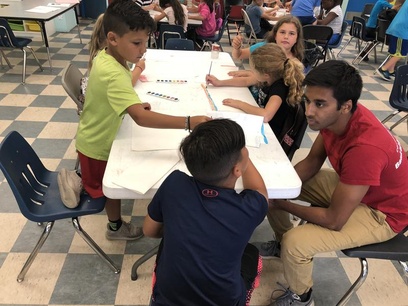 Shaunak Mishra, 17, right, works with second grade students during an art class at the Boys & Girls Club summer camp in Miami where he's a counselor. His paid internship there is part of a national selective leadership program run by Bank of America.