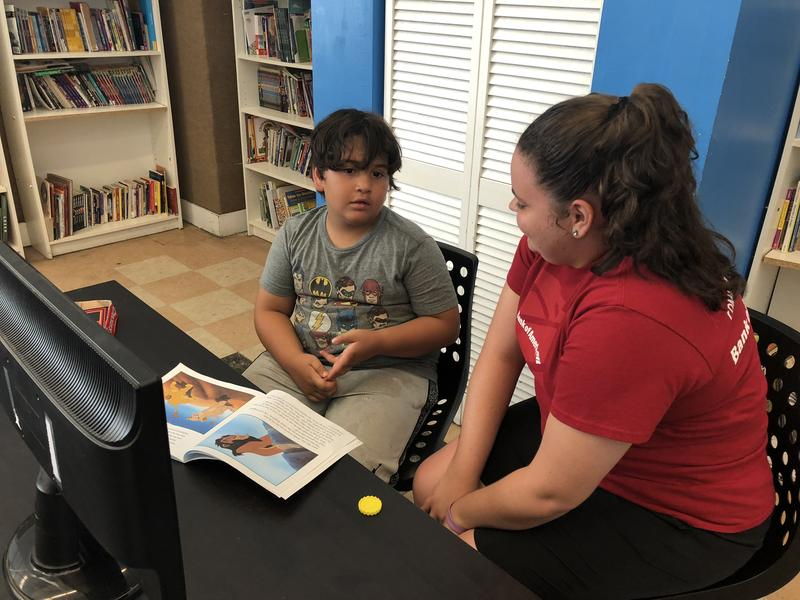 """Stephanie Torres, 18, helps a student read """"The Lion King"""" during a literacy class at the Boys & Girls Club summer camp in Kendall. She's also part of the Bank of America program."""