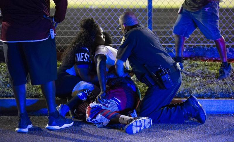 A police officer applies pressure to the wound of a gunshot victim. Two adults were shot the night of Friday Aug. 17 at a football game between Palm Beach Central and William T. Dwyer high schools, authorities said.