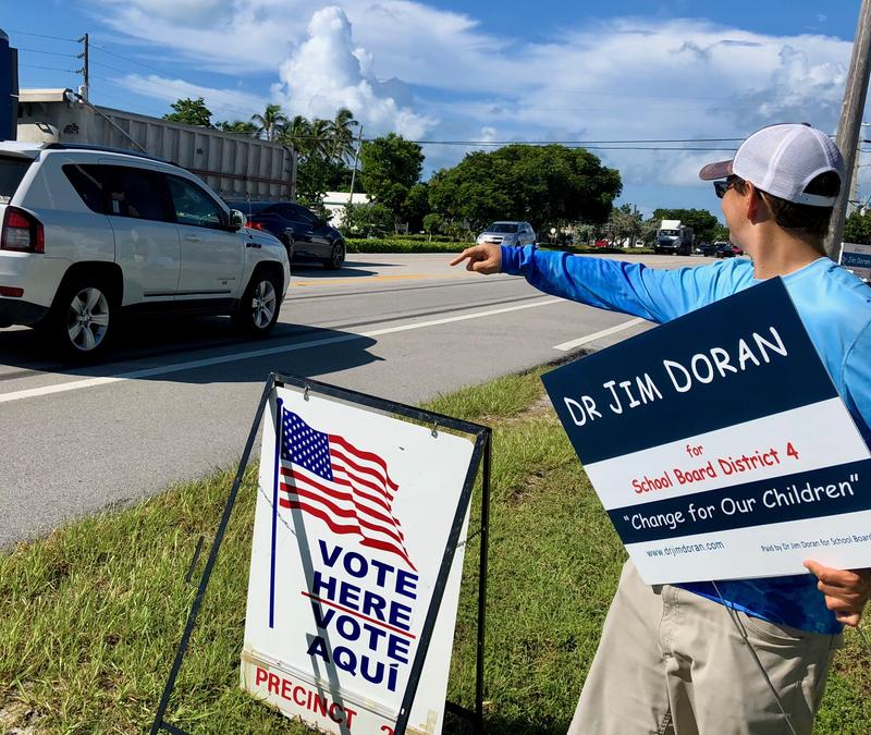 Joe Cianciolo, 31, holds a sign supporting a Monroe County school board candidate as he tries to get the attention of drivers on the Overseas Highway outside a polling station in Islamorada.
