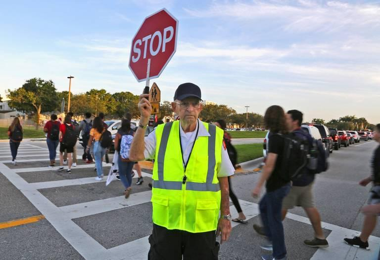 Crossing guard Tony Sorrentino helps Marjory Stoneman Douglas High School students return Wednesday for the first day of school. The next day, a student pulled the fire alarm.