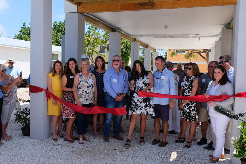 Maggie Whitcomb, the founder of the Florida Keys Community Land Trust, cuts the ribbon on the group's first home completed on Big Pine Key.