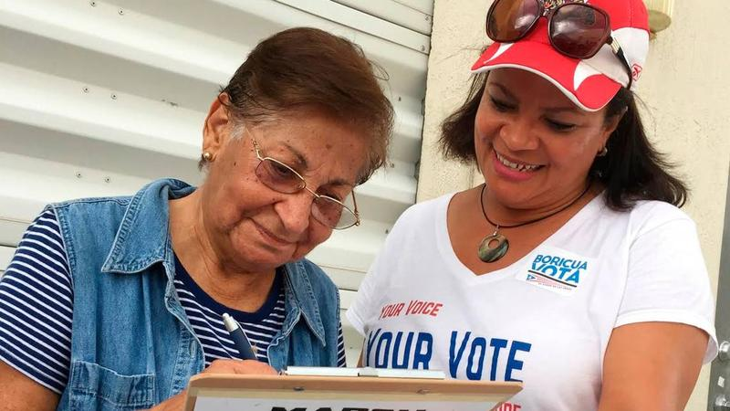 In April 2018, Marisol Zenteno, right, from the League of Women Voters, helps with registering Aida Merced Lopez, who moved to Miami from Puerto Rico in April 2017, before Hurricane Maria ravaged the island.