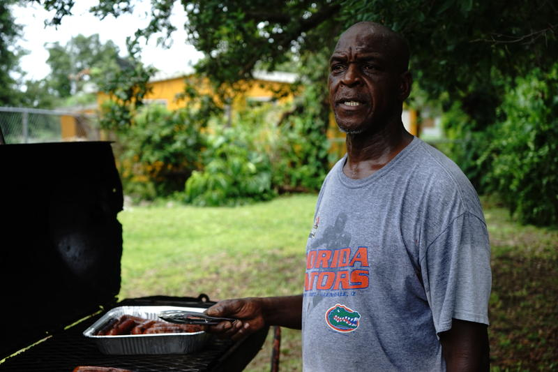 Rodney Jackson, a lifelong Brownsville resident, grills hot dogs to feed to volunteers.