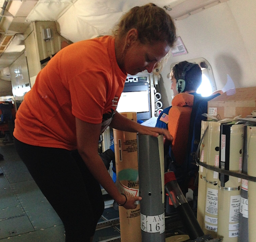 Johna Rudzin of the University of Miami preparing an oceanographic sensor instrument on a National Oceanic and Atmospheric Administration (NOAA) hurricane hunter plane over the Caribbean.