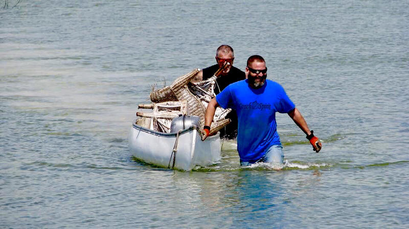 Two volunteers from The Conch Republic Marine Army cleanup a canal in the Florida Keys in April.
