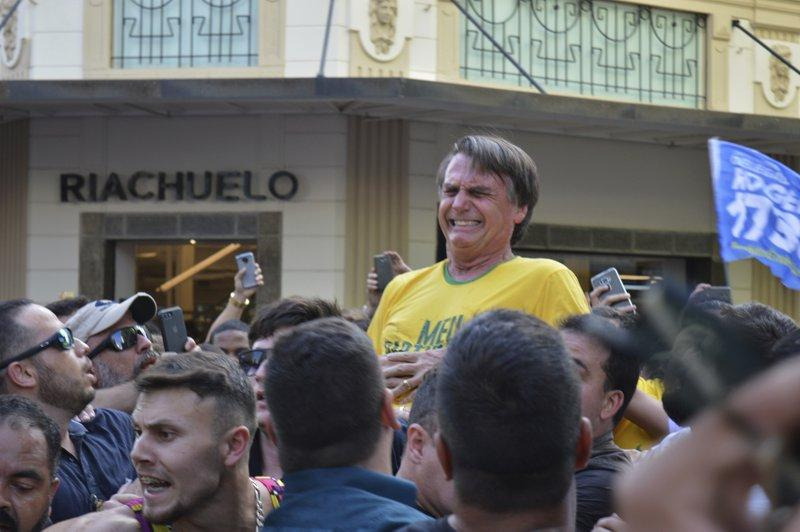 Presidential candidate Jair Bolsonaro grimaces right after being stabbed in the stomach during a campaign rally in Juiz de Fora, Brazil, Thursday, Sept. 6, 2018.